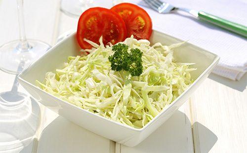 Салат из свежей капусты в белой тарелке