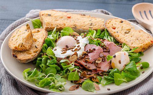 Салат с гренками и копченым мясом на тарелке